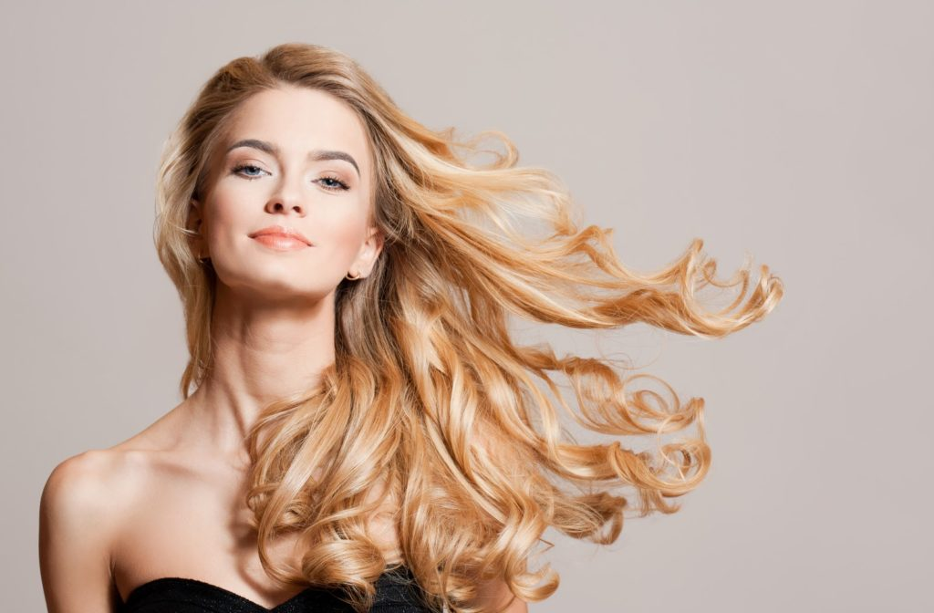 Young woman showing off her long and healthy blonde hair