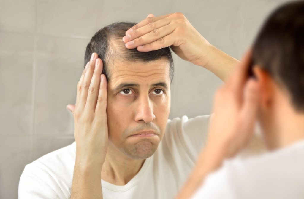 Unhappy man looking in the mirror touching his proceeding hairline