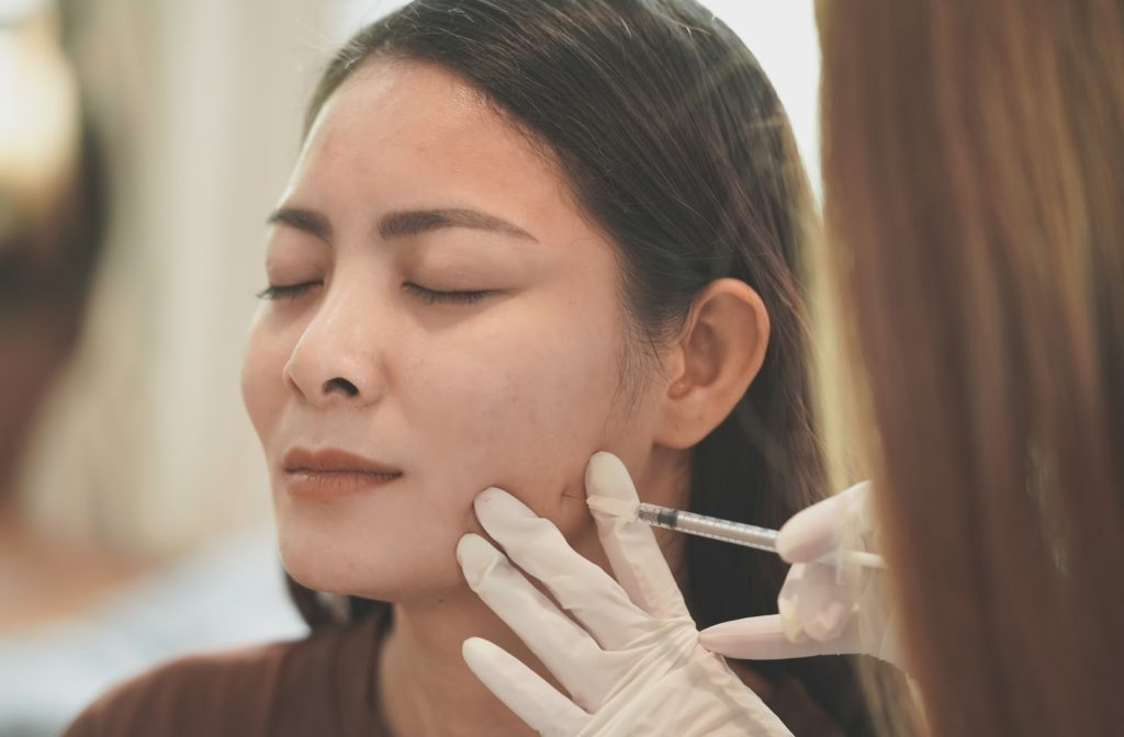 Woman experiencing pain when receiving botox from professional.