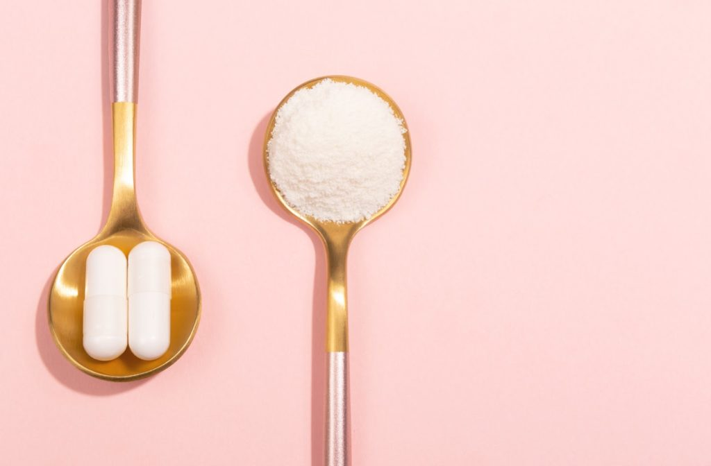 Collagen powder and pills displayed on spoons with pink background