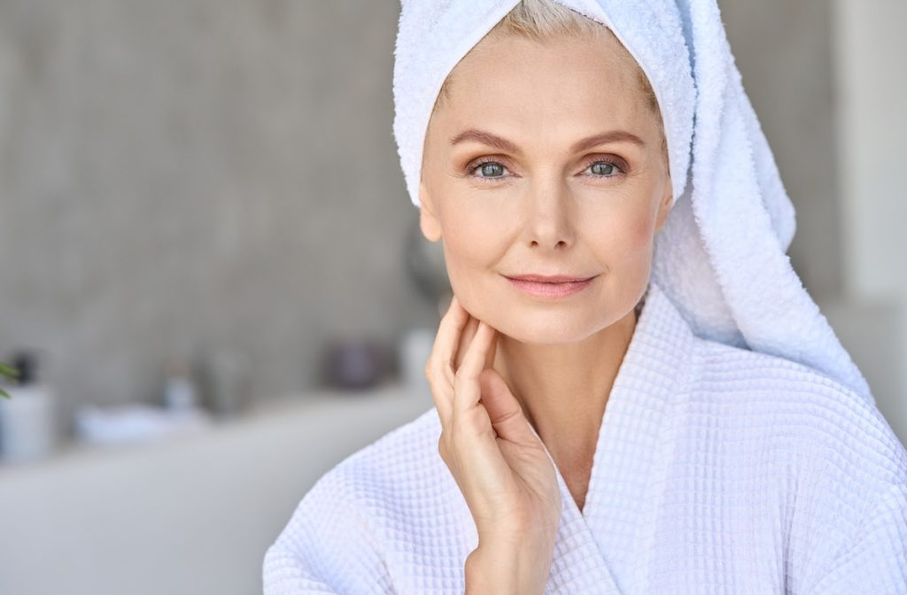 Happy middle aged woman touching moisturized skin while wearing bathrobe and towel on head.