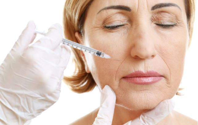 Older women receiving beauty injection in her face from professional