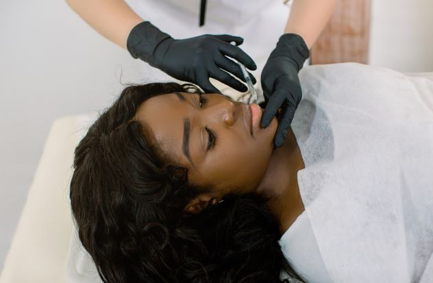 Young women receiving Botox injection in face from professional at clinic